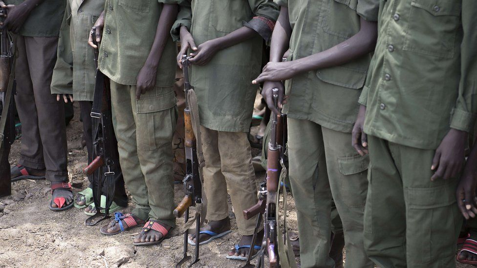 A file photo taken on February 10, 2015 shows young boys, child soldiers, preparing to lay down their arms at a ceremony of disarmament, demobilisation and reintegration in Pibor overseen by Unicef and partners.