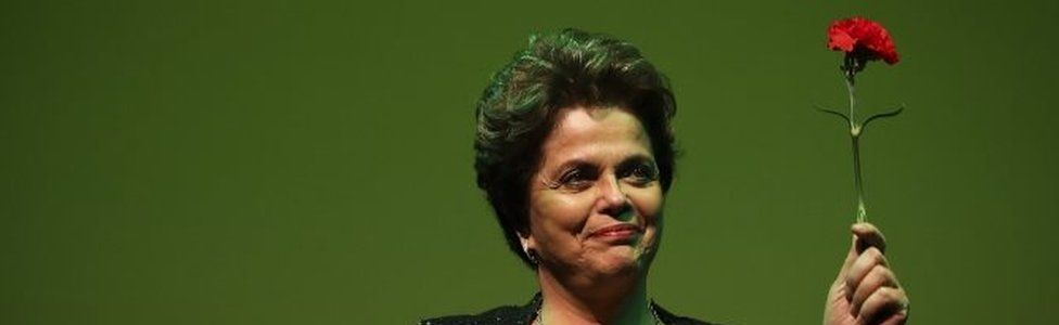 """Former president of Brazil Dilma Rousseff holds a red carnation as she attends the conference """"Neoliberalism, inequality, democracy under attack"""" at Trindade Theater, in Lisbon, Portugal, 15 March 2017."""