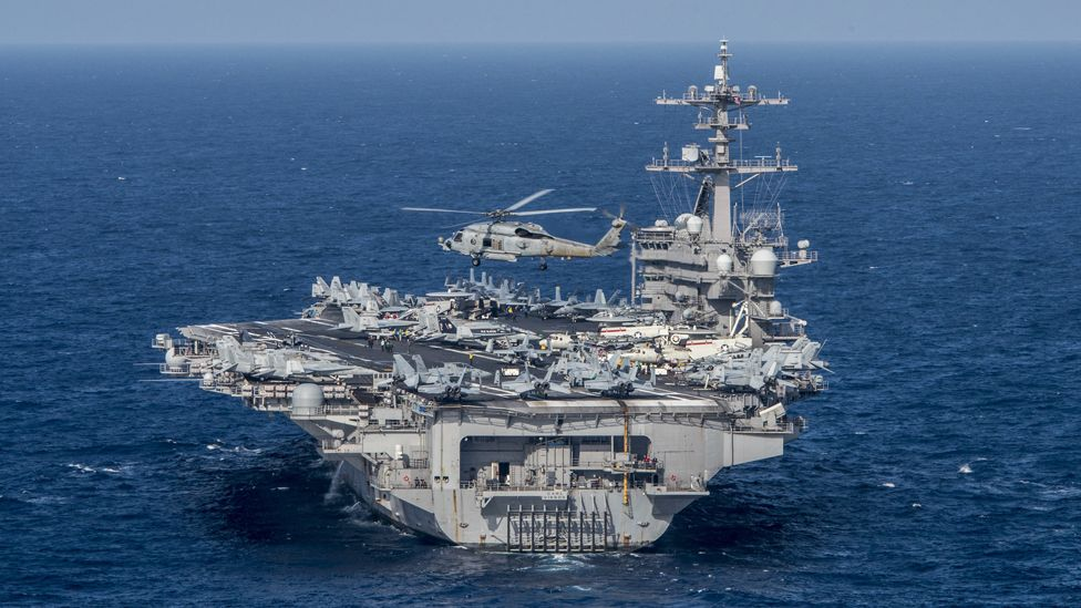 """A handout photo made available by the United States Department of Defense (DoD) shows an MH-60R Sea Hawk from the Helicopter Maritime Strike Squadron (HSM) 78 """"Blue Hawks"""" flying near the aircraft carrier USS Carl Vinson (CVN 70) at sea in the Philippine Sea, 24 April 2017"""