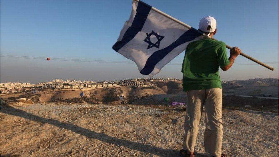 Jewish youth holds Israeli flag near Jewish settlement of Maale Adumim (file photo)