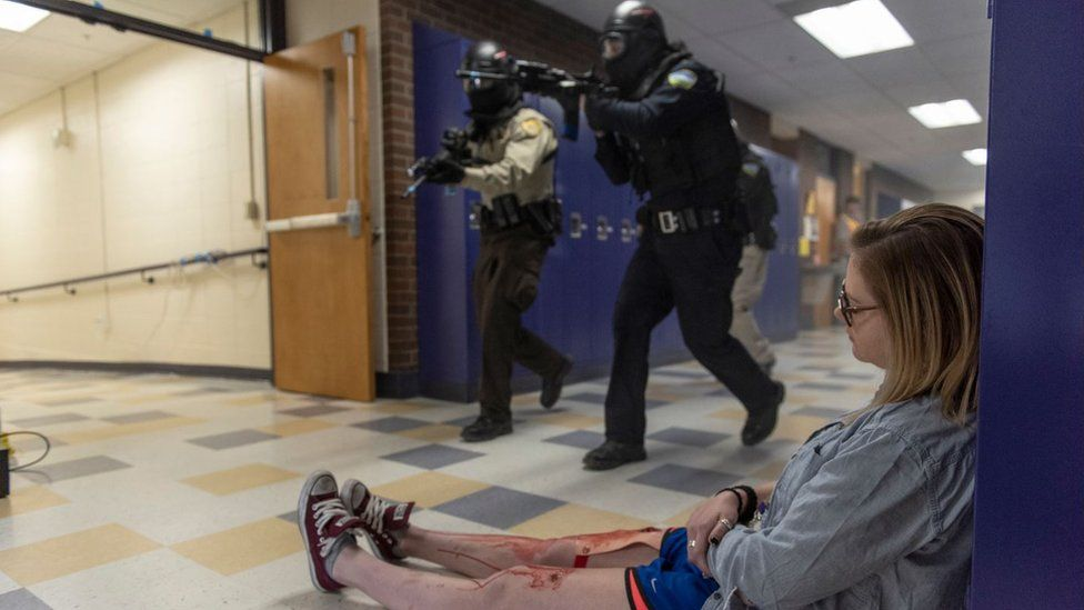 A student with fake blood on their legs slumped on the floor during an active shooter drill in California