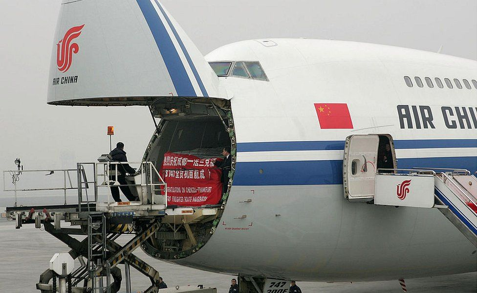 Workers load a Boeing 747-200 freighter of Air China at Chengdu Shuangliu International Airport