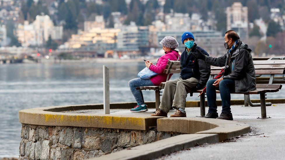Two man wearing protective face mask converse on a park bench along the seawall at Stanley Park