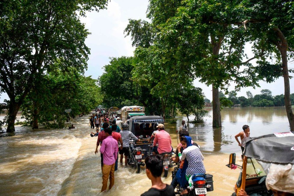 Indian residents drive their vehicles along a flooded road following heavy monsoon rains at Sitamarhi district in the Indian state of Bihar.