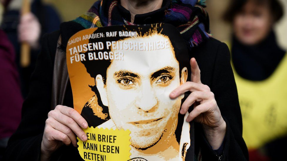 Amnesty International activist holds picture of Saudi blogger Raif Badawi during protest in Berlin on January 29, 2015
