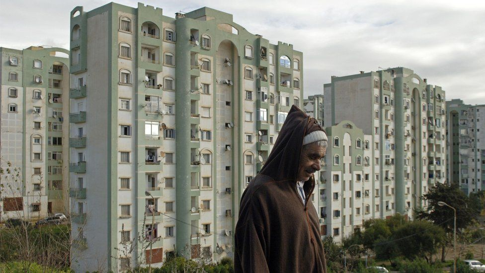 An Algerian man walks in one of the many new residential districts outside the capital Algier