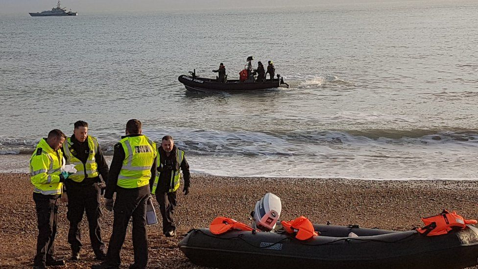 Border force officials by a dinghy