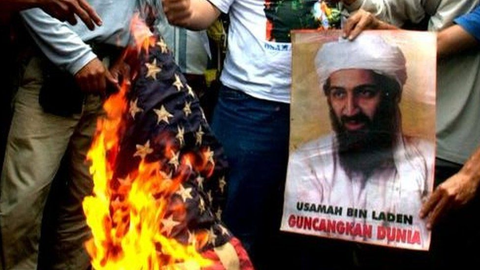 Anti-US protesters burn an American flag next to a portrait of Osama bin Laden in front of the U.S. embassy in Jakarta, Indonesia, Tuesday, Oct. 9, 2001.
