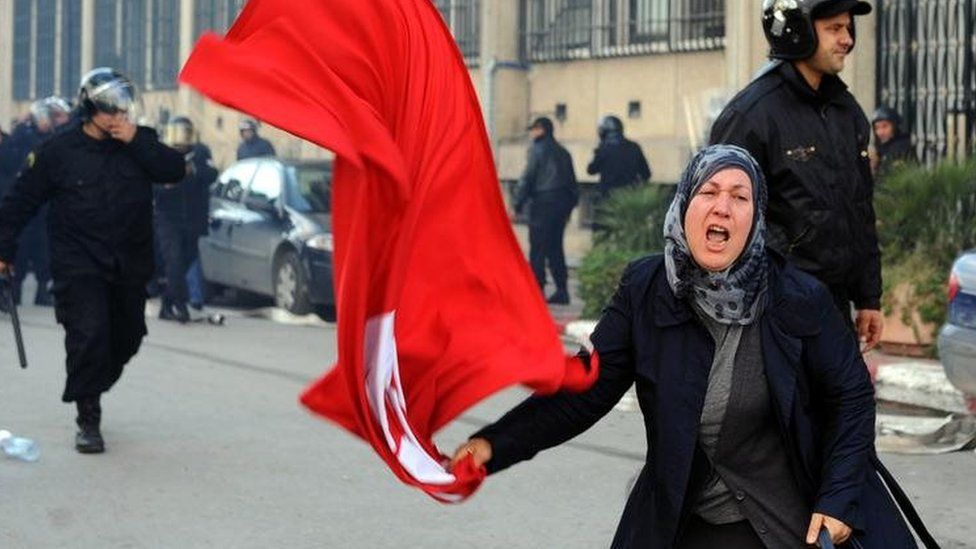 A woman waves Tunisia's national flag during clashes with police in the capital Tunis. Photo: 14 January 2011