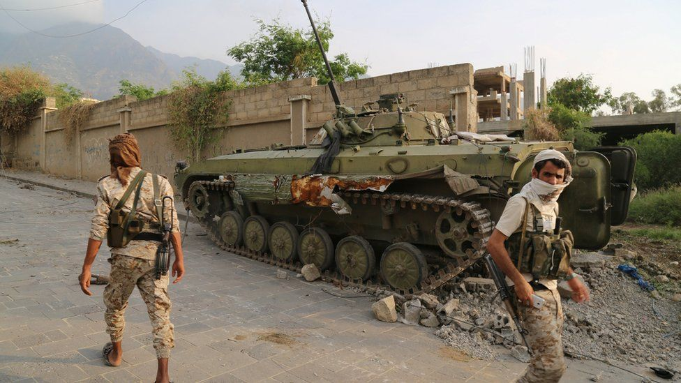 Pro-government fighter army troops walk in a position they retook from Houthi fighters near the Republican Palace in the north-western city of Taiz