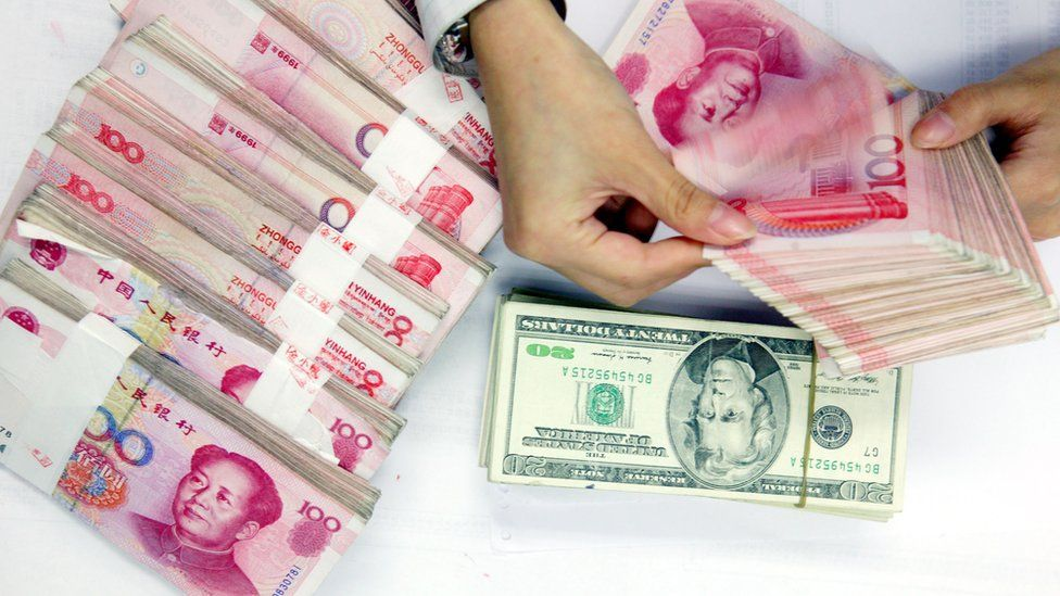 A clerk counts stacks of Chinese yuan and U.S. dollars