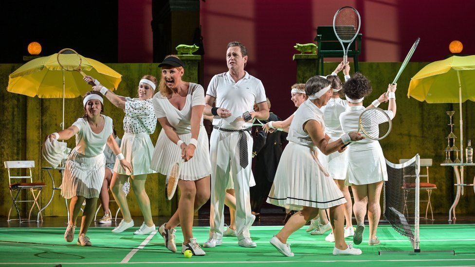 Mr Chaundy is pictured in white trousers and a white polo shirt on stage, surrounded by dancers prancing around him in tennis apparel, brandishing racquets