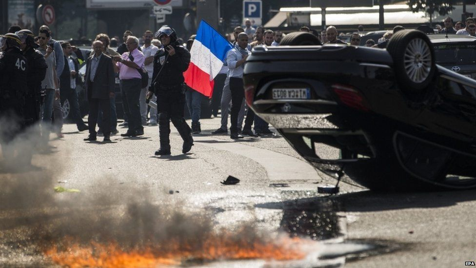 An UberPop vehicle overturned by French taxi drivers as they clash with riot police