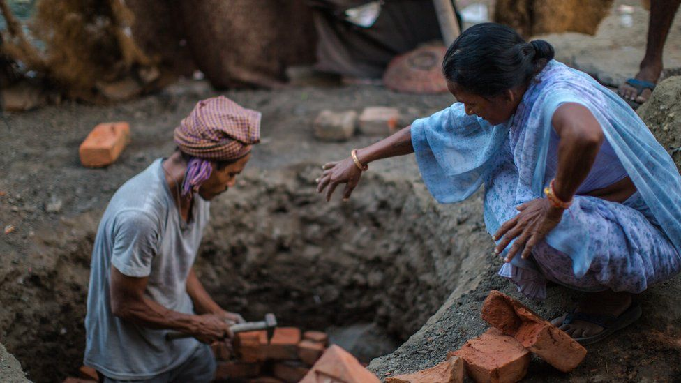 A woman clad in a sari helps a mason build a toilet in India's Kanpur city in 2014.