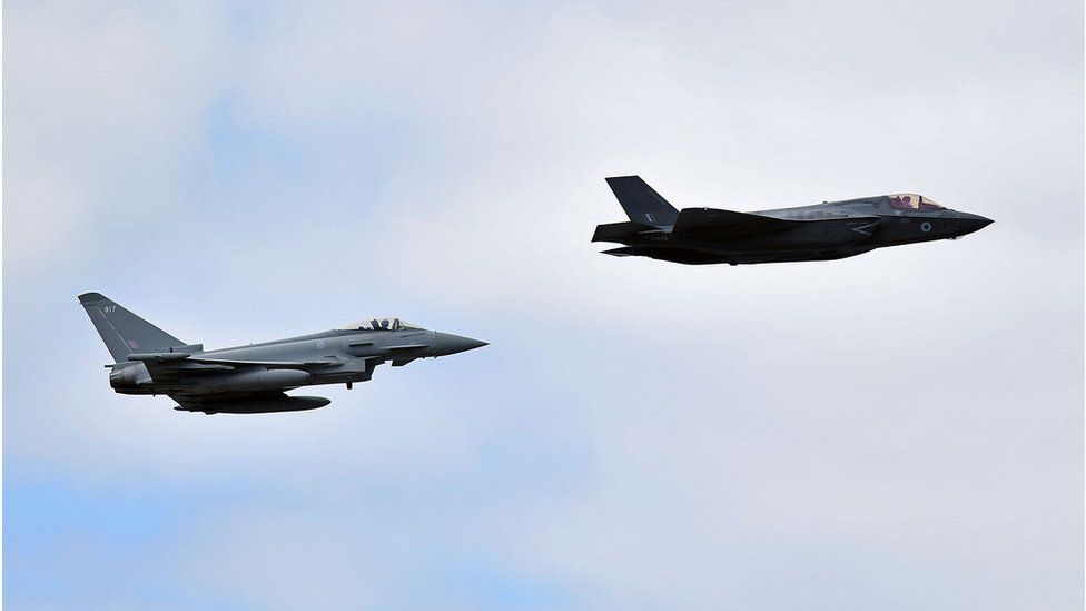 A British Royal Air Force (RAF) Lockheed Martin F-35 Lightning II (R) and a Eurofighter Typhoon aircraft perform a fly-past