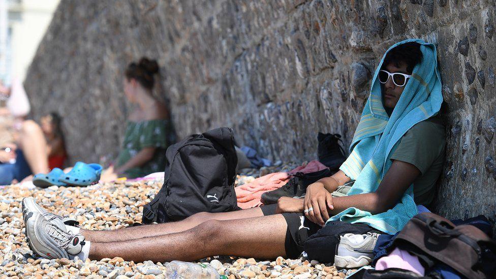 A man in the shade on Brighton beach