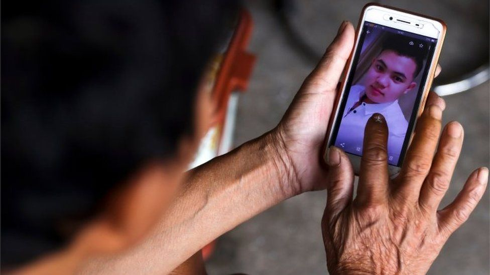 The father of Hoang Van Tiep shows his picture on a mobile phone