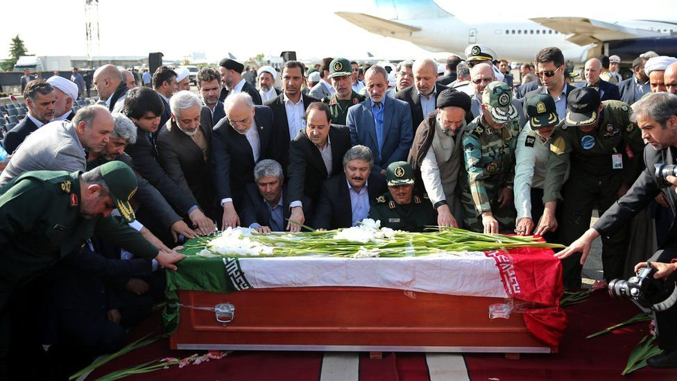 Iranian officials touch the coffin of a Hajj pilgrim killed in a stampede in Mecca (3 October 2015)