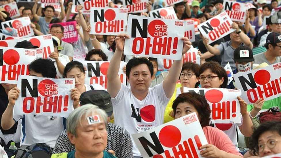 """South Korean protesters hold signs reading """"No Abe!"""" during an anti-Japanese rally"""