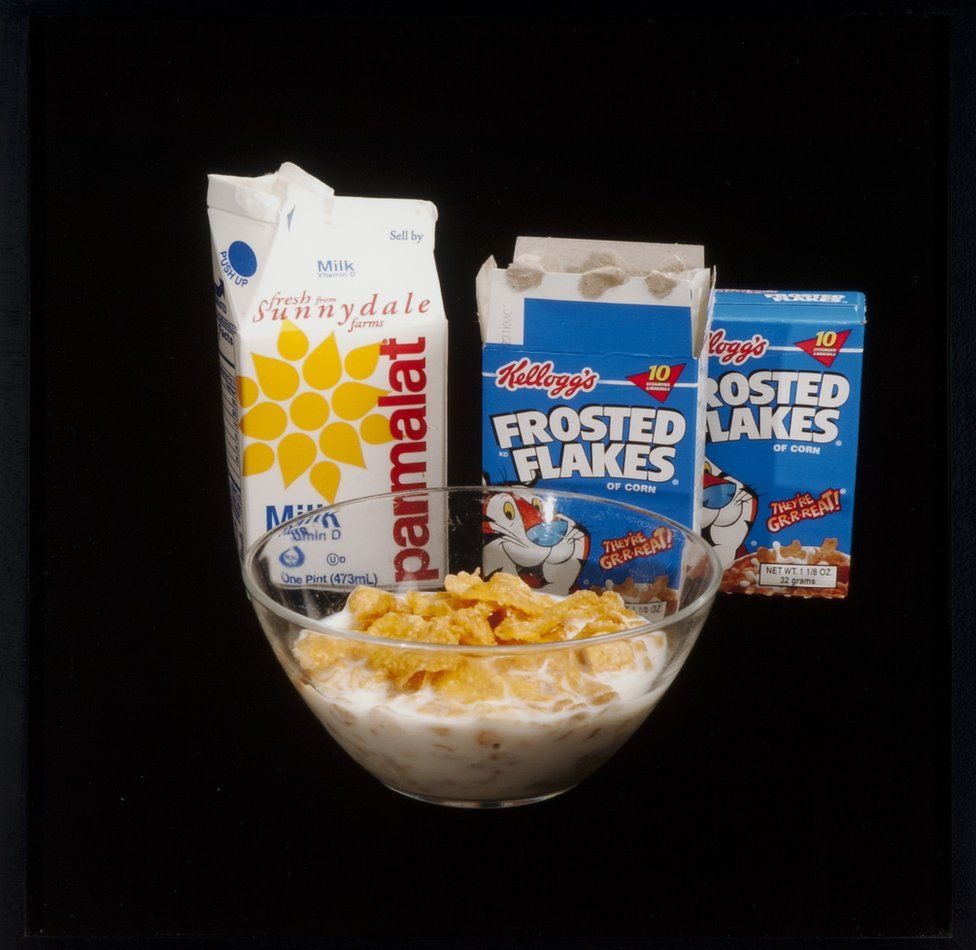 Un tazón de cereal con leche, una caja de leche y dos cajas de hojuelas.