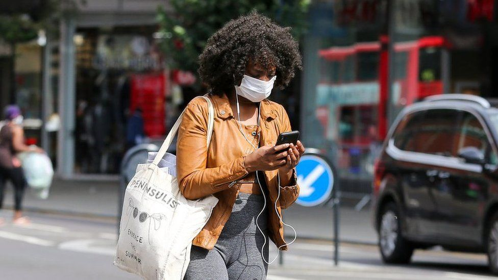 A woman wearing a face mask is seen using a mobile phone while walking on the street.