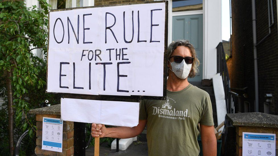 """A protester holds a placard saying """"One rule for the elite"""" outside Cummings' home in London on 25 May 2020"""