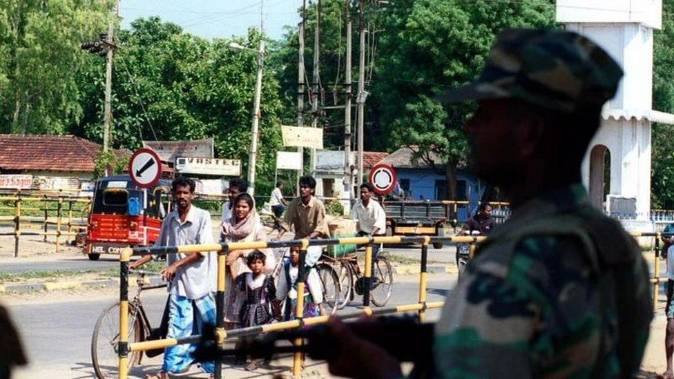 A Sri Lankan army soldier looks on as civilians walk out of Vavuniya town, 210 kilometres (130 miles) north of the capital, Colombo, Thursday November 11, 1999.