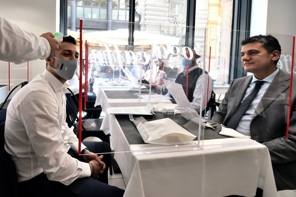 A waiter checks a customer's temperature in a restaurant