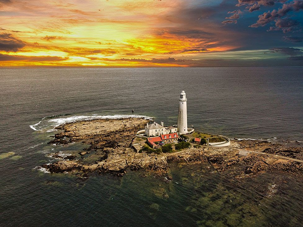 A lighthouse on a rocky outcrop with a sunrise in the background