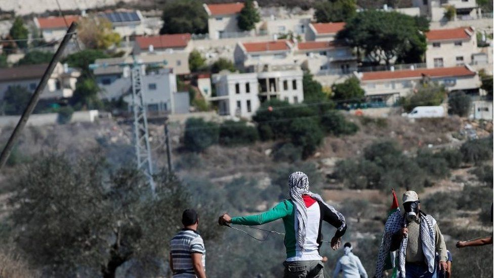 Palestinians look towards a Jewish settlement in the occupied West Bank (file photo)