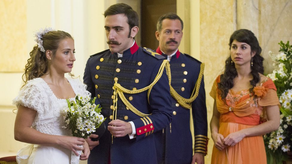 Otávio. played by Pedro Henrique Muller, looks at Lídia Benedito, played by Bruna Griphão