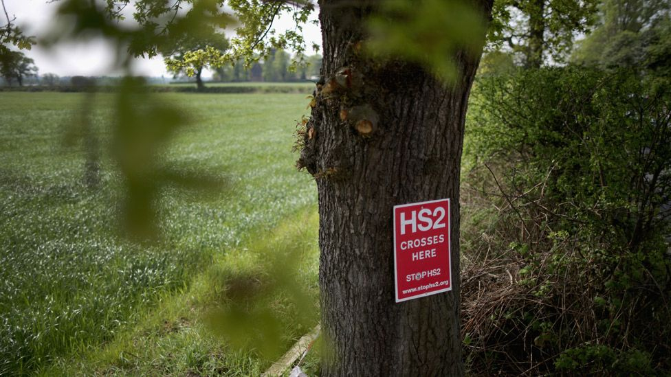Poster saying HS2 crosses here on a tree in the countryside