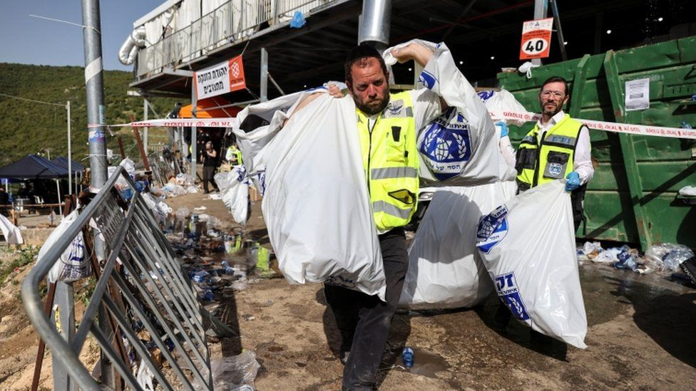 A rescue worker carries plastic bags with hats of Orthodox Jews