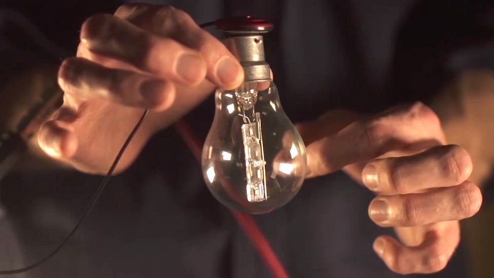 Man flicking a light bulb and recording the sound it makes