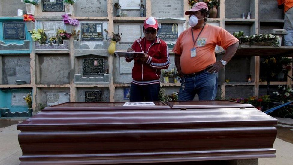 Workers stand next to the coffin of a mudslide victim on 6 October, 2015