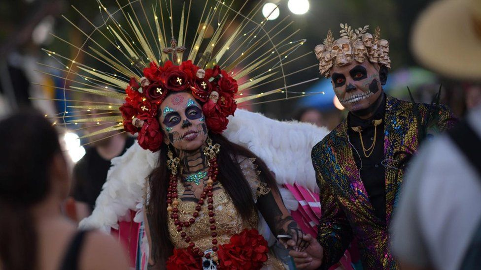 A couple in full day-of-the-dead dress including light up headband