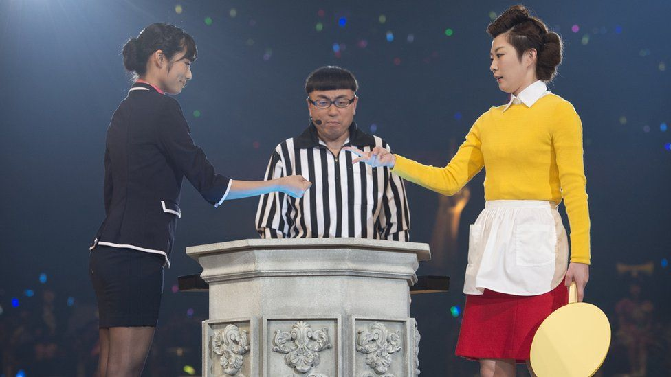 "Two band members compete during the rock-paper-scissors tournament in 2015, with an umpire looking on. The woman on the right has just thrown ""scissors"", losing to ""rock"" on the left."