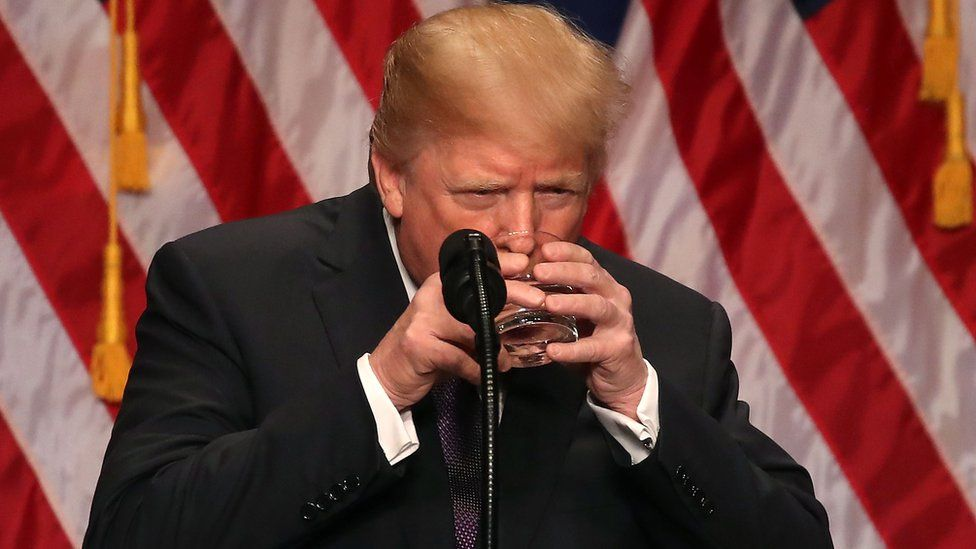 U.S. President Donald Trump drinks from a water glass he holds with two hands during a speech at the Ronald Reagan Building on December 18, 2017 in Washington, DC.