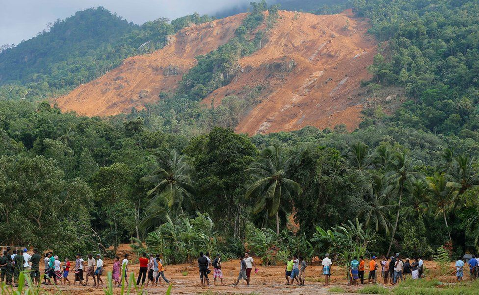Sri Lankan landslide survivors and others walk through the mud below the Elangipitiya village landslide, with the mountainside in the background. Photo taken on 18 May 2016.