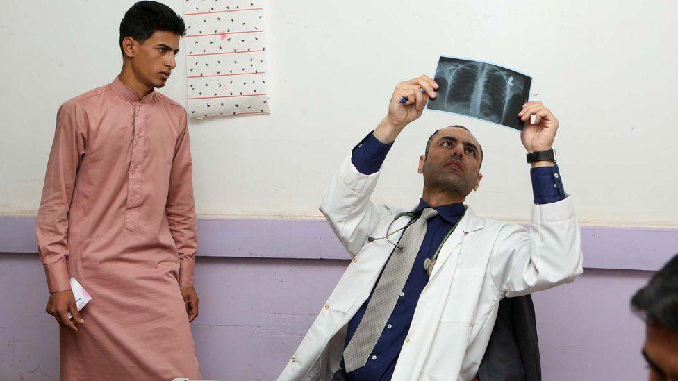 Dr Laith Al-Rubaiy inspects an X-ray as a boy looks on