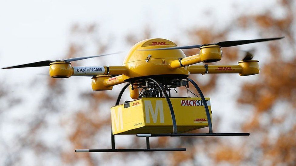 A quadcopter DHL drone arrives with a small delivery at Deutsche Post headquarters in Bonn, Germany: Dec 2013