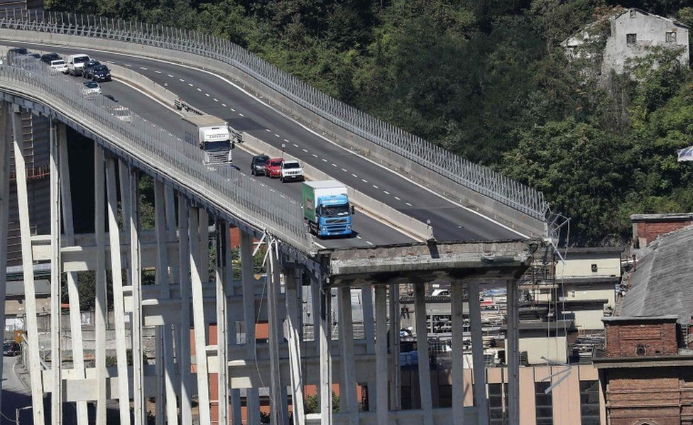 A picture of the Morandi motorway bridge showing the missing area and vehicles close to the edge
