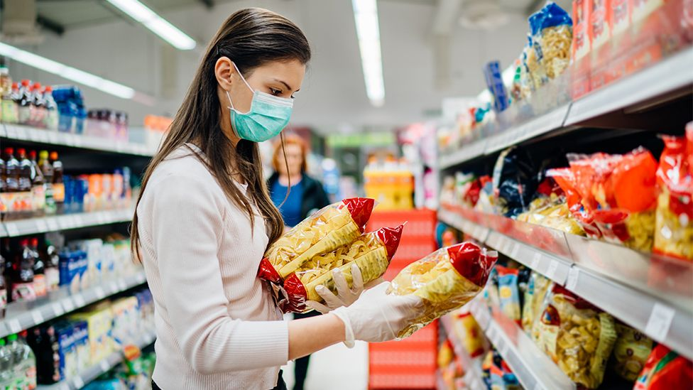 Woman in mask buying pasta