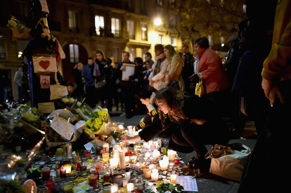 Members of the public view candles and tributes left opposite the main entrance of the Bataclan concert
