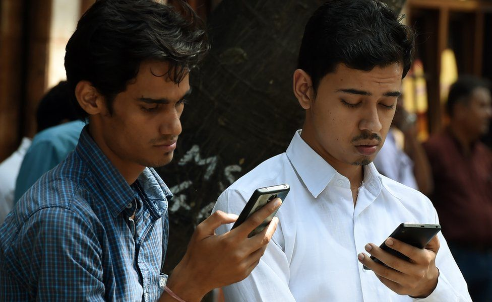 Indian pedestrians check their cellphones as they stand in front of the Bombay Stock Exchange (BSE) in Mumbai on September 29, 2016.
