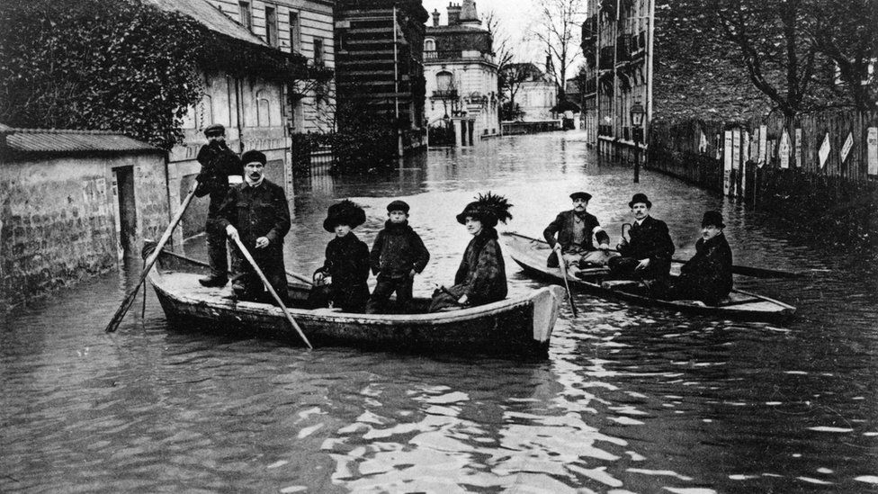 people in heavy old-fashioned outfits and hats on boats in a narrow city street
