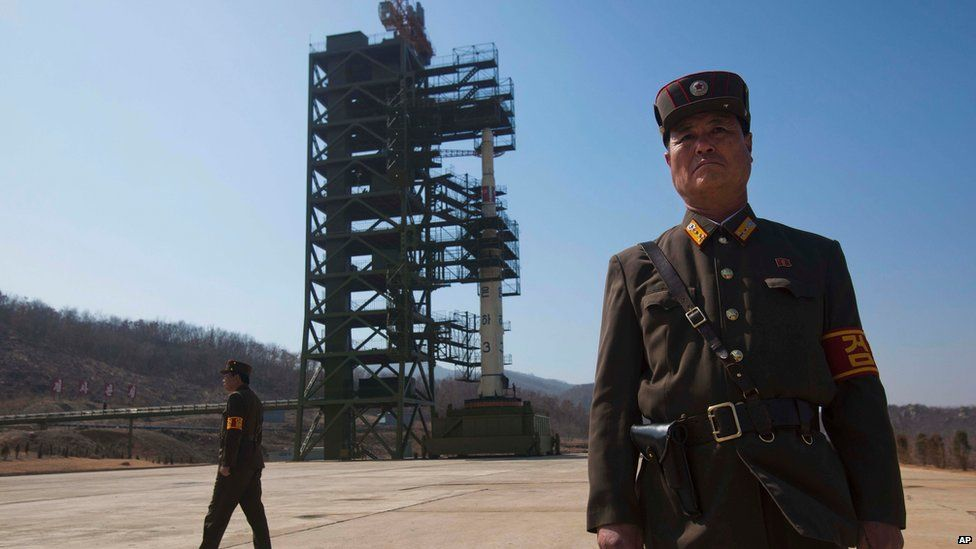 """North Korean soldiers stands in front of the country""""s Unha-3 rocket,"""