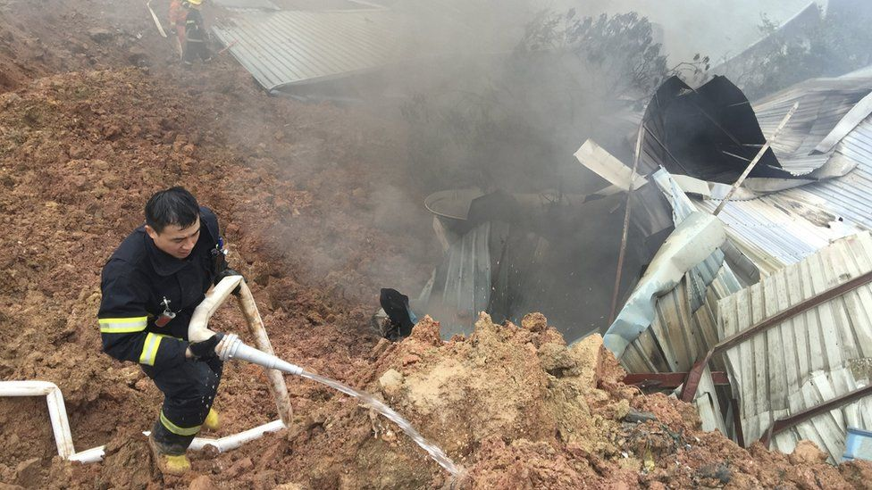 Rescuers spray liquid next to damaged sheds at the site of a landslide at an industrial park in Shenzhen, Guangdong province, China, December 20, 2015.