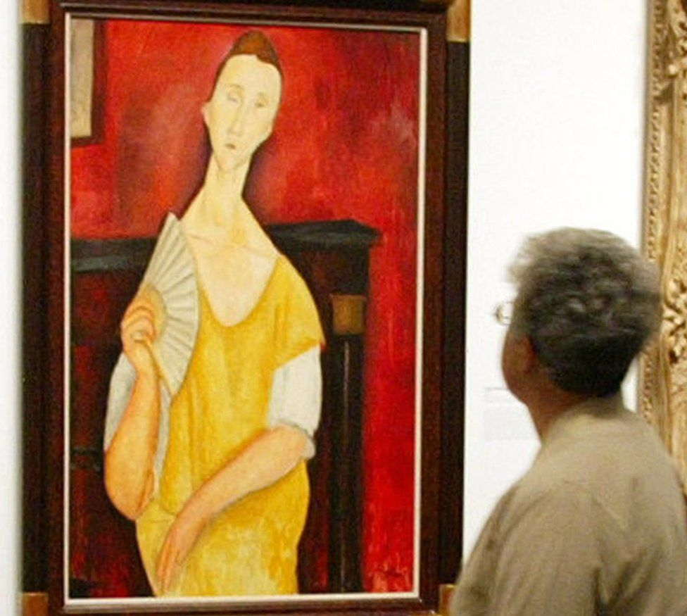A visitor looking at the painting La femme à l'éventail (Woman with a Fan) by Amedeo Modigliani