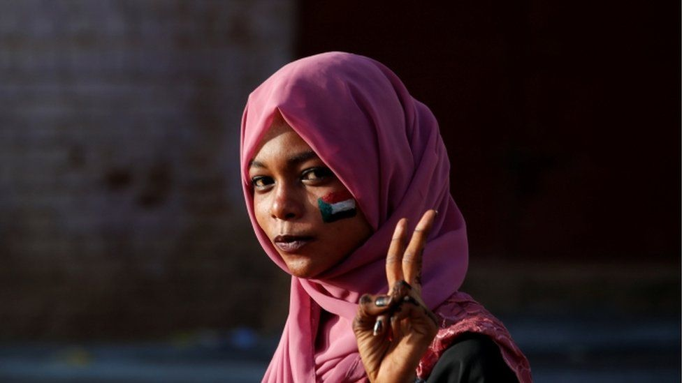 A Sudanese protester holds up two fingers in a victory sign outside the defence ministry in Khartoum